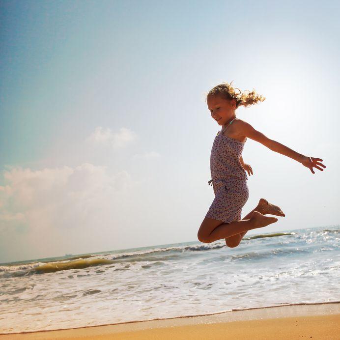 海岸でジャンプする少女