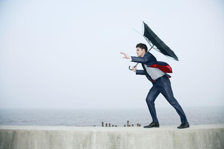 暴風の中を歩く男性