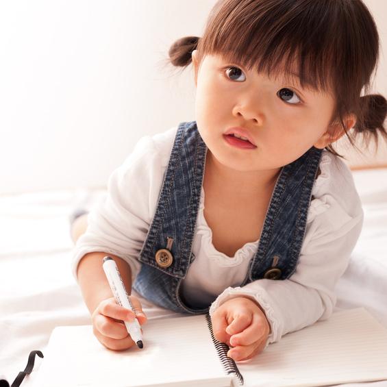 紙に何かを書こうとする女の子